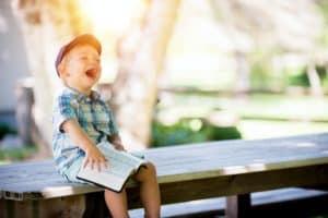 ילד צוחק ושמח עם ספר פתוח